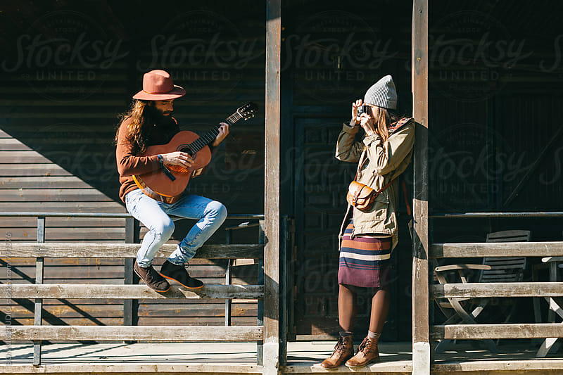 Hipster couple enjoying a sunny day on a cabin porch. by BONNINSTUDIO for Stocksy United