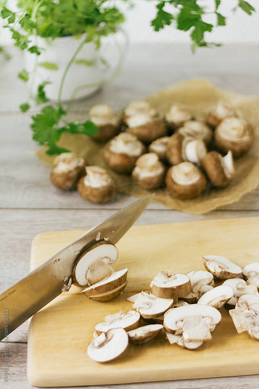 Chopping chestnut mushrooms vertical by Kirsty Begg for Stocksy United