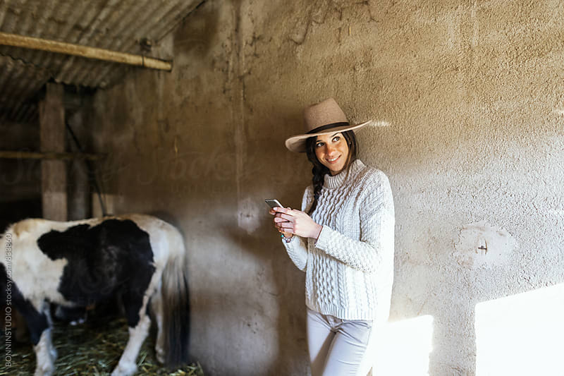 Portrait of a woman farmer using her phone on animal stable. by BONNINSTUDIO for Stocksy United