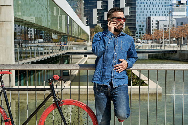 Young man using his smartphone beside a fixed gear bicycle by Guille Faingold for Stocksy United