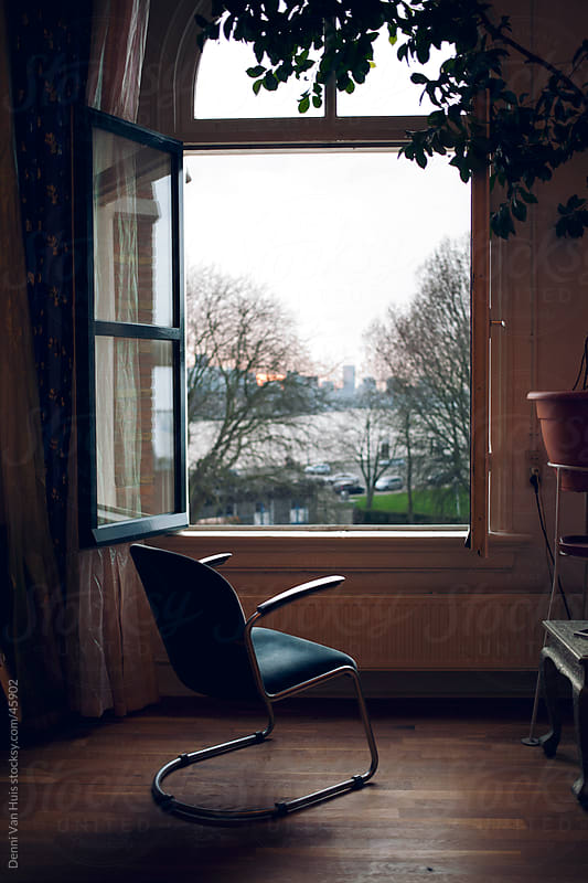 Empty chair in front of a open window with a view by Denni Van Huis for Stocksy United