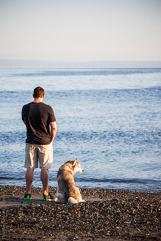 Man with his dog on the beach by Suprijono Suharjoto for Stocksy United