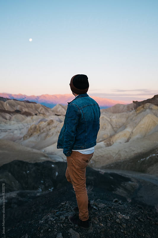 young man walking through national park at sunrise by Jesse Morrow for Stocksy United