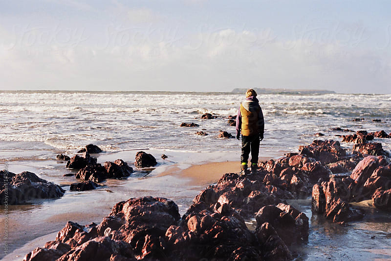Male child standing on rocks at the edge of the sea in winter by Helen Rushbrook for Stocksy United
