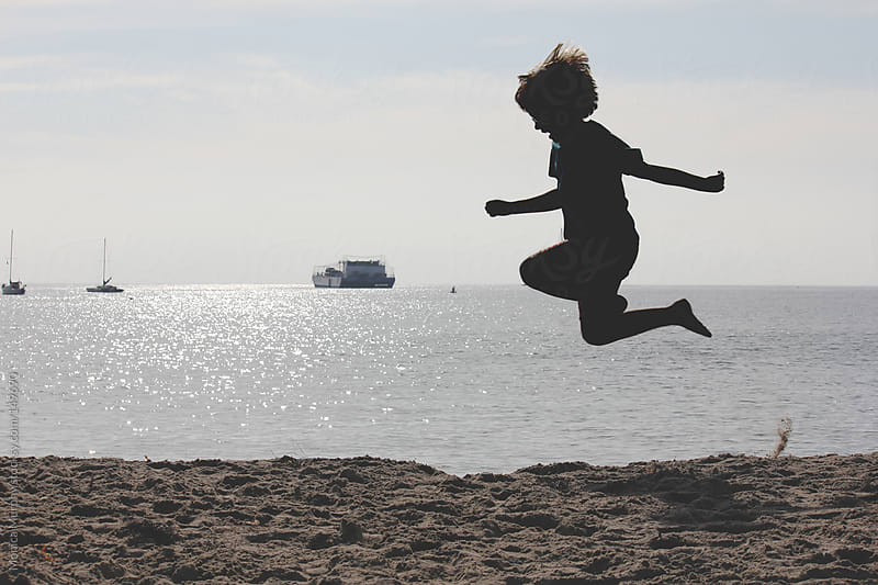 Silhouette of boy jumping at the beach by Monica Murphy for Stocksy United