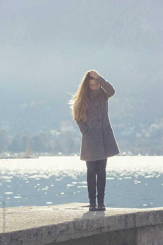 Young woman standing on a dock near the sea by B & J for Stocksy United