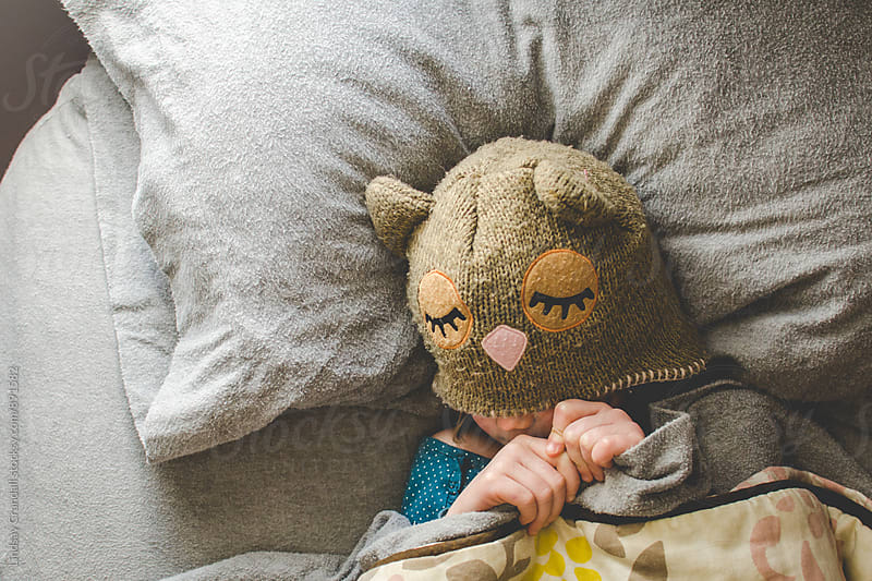 Little girl in owl hat lying in bed resting by Lindsay Crandall for Stocksy United
