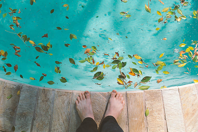Looking down at toes and a leaf covered swimming pool. by Lucas Saugen for Stocksy United