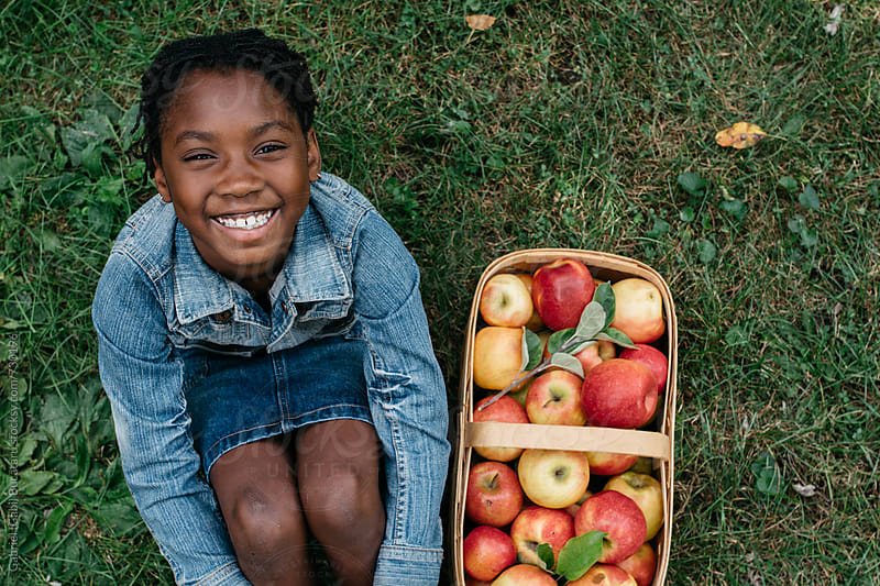 Smiling African American girl next to a basket of apples by Gabriel (Gabi) Bucataru for Stocksy United