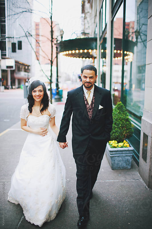 Newlywed Couple Walks Downtown by Kevin Russ for Stocksy United