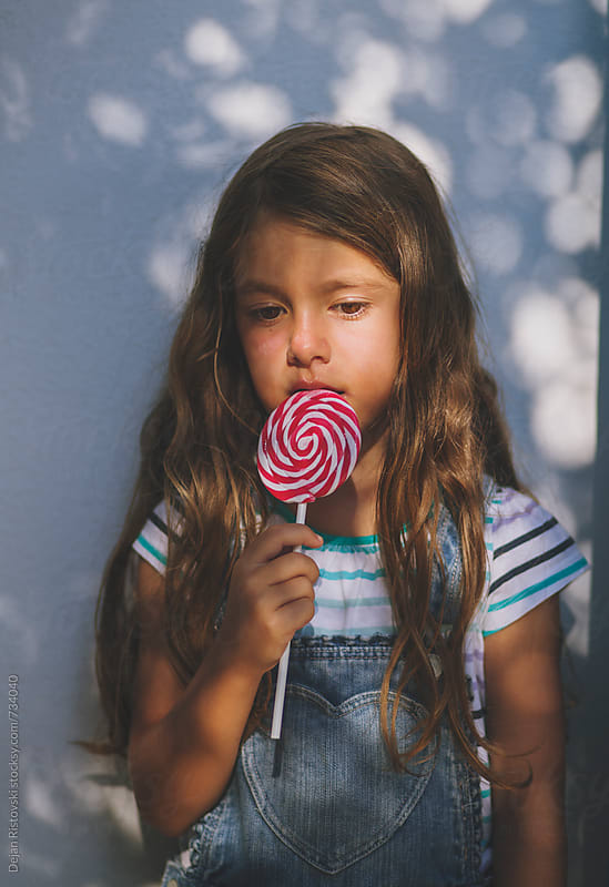 Child eating lollipop by Dejan Ristovski for Stocksy United