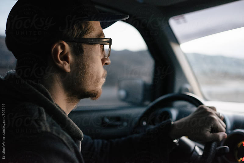 Man focused driving a car by Kristine Weilert for Stocksy United