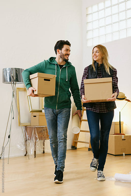 Young couple carrying boxes for moving into a new home.  by BONNINSTUDIO for Stocksy United
