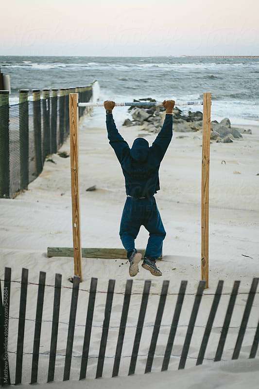 Man in sweat shirt doing pullup exercises on beach outdoors by Matthew Spaulding for Stocksy United