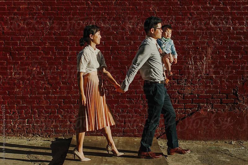 Family Walking in front of Red Wall by Sidney Morgan for Stocksy United