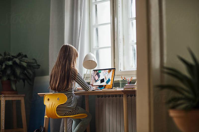 Girl Doing Homework on Her Computer by Lumina for Stocksy United