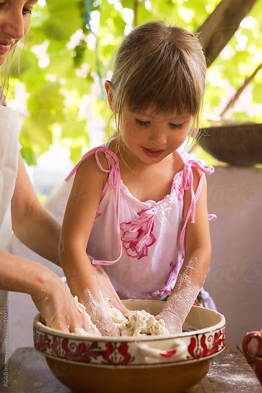 Mother and daughter hand kneading bread  by RG&B Images for Stocksy United
