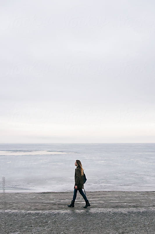 Long-haired woman walking along shoreline by Danil Nevsky for Stocksy United