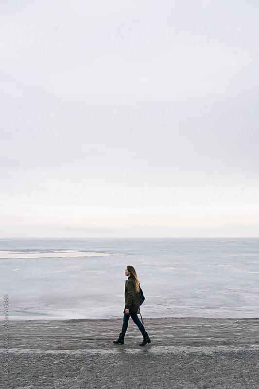 Long-haired woman walking along shoreline by T-REX & Flower for Stocksy United