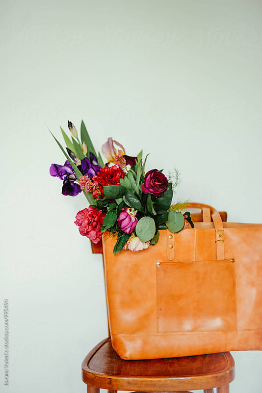 bouquet in a leather bag by Jovana Vukotic for Stocksy United