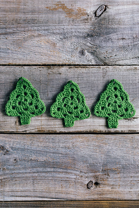 Three little crocheted Christmas trees on rustic wood background - vertical by Jacqui Miller for Stocksy United