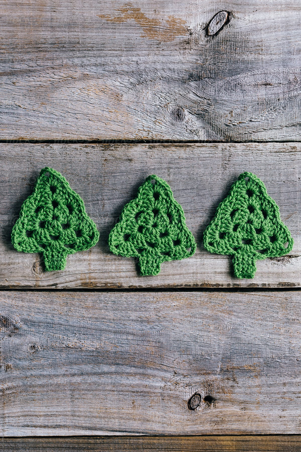 Three Little Crocheted Christmas Trees On Rustic Wood Background Vertical By Jacqui Miller Christmas Decoration Stocksy United
