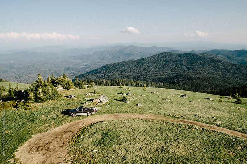 Truck parked on top of a grassy mountain top by Justin Mullet for Stocksy United
