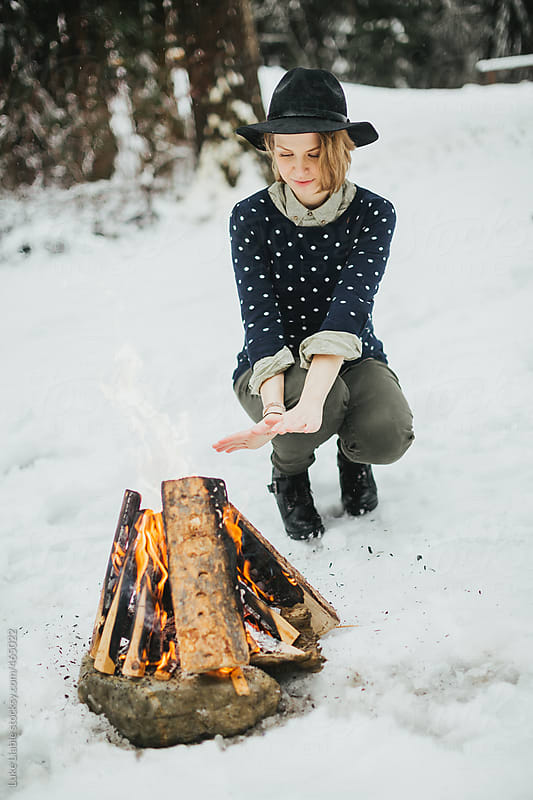 Young fashionable women sitting warming hands by fire in the snow by Luke Liable for Stocksy United