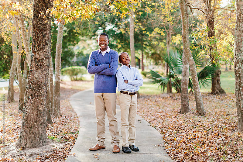 Portrait of two sibling boys standing back to back by Kristen Curette Hines for Stocksy United