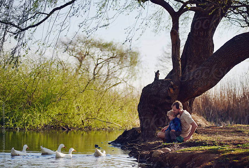 feeding ducks family by Daxiao Productions for Stocksy United