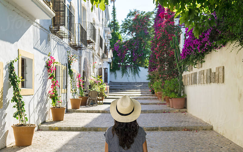 Young woman walking down a street in Ibiza by ACALU Studio for Stocksy United