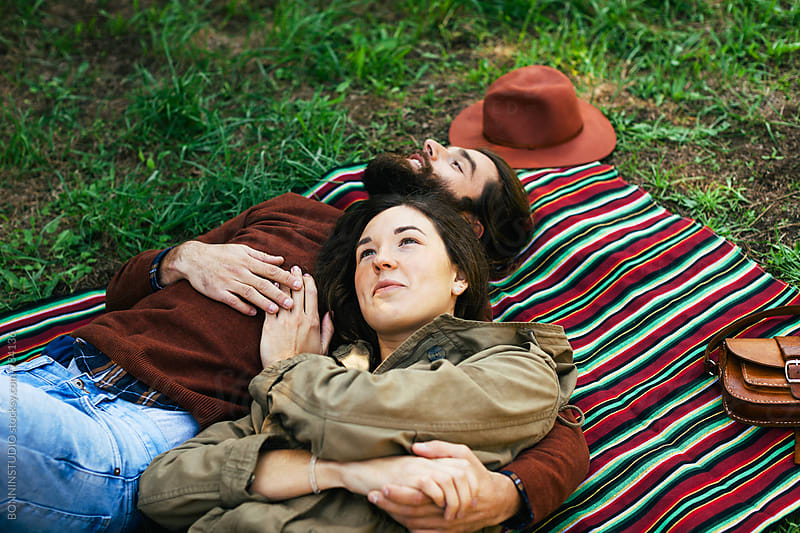 Overhead of couple embracing together resting on a striped blanket in the park. by BONNINSTUDIO for Stocksy United