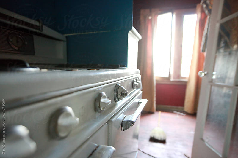 Abandoned vintage house showing stove and looking through doorway by Dina Giangregorio for Stocksy United