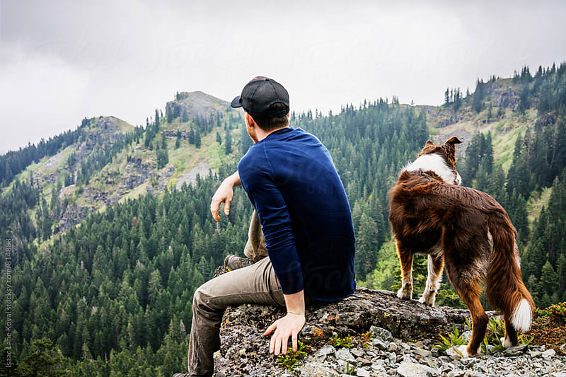 Man and dog sitting on edge of cliff by Isaac Lane Koval for Stocksy United