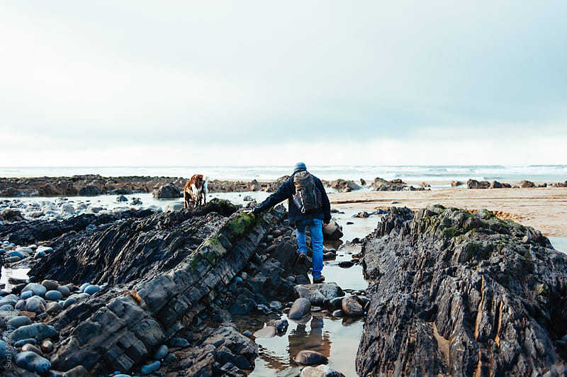 Man and dog climbing on rocks at the beach by Suzi Marshall for Stocksy United