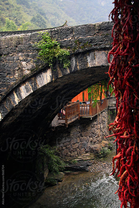 Bundle of red chili pepper and stone bridge, river and traditional Chinese wooden houses behind it by Alice Nerr for Stocksy United