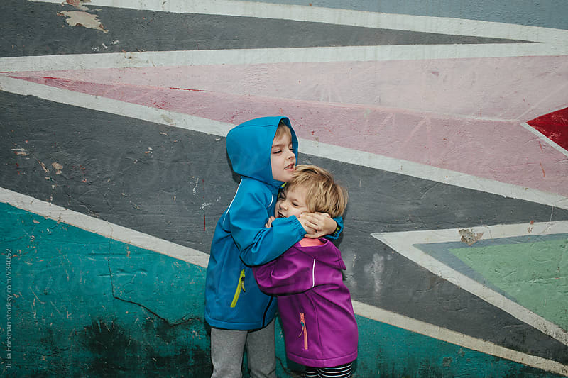 Brother squeezes his sister in front of a brightly painted wall.  by Julia Forsman for Stocksy United