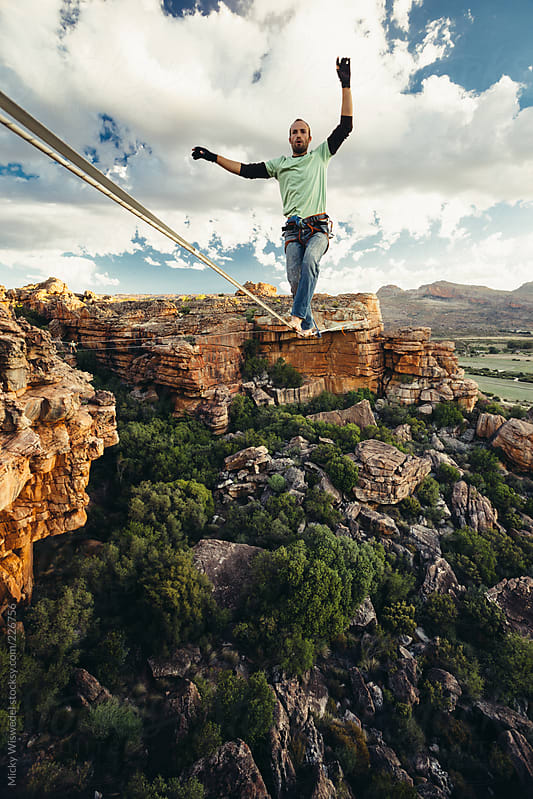 Man balance walking on a highline or tight rope high over a mountain valley at sunset by Micky Wiswedel for Stocksy United