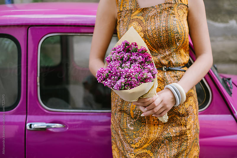 Close up of a Woman Holding Flowers in Front of the PInk Car by Aleksandra Jankovic for Stocksy United