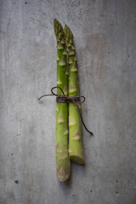 Raw asparagus on concrete background by Todd Beltz for Stocksy United