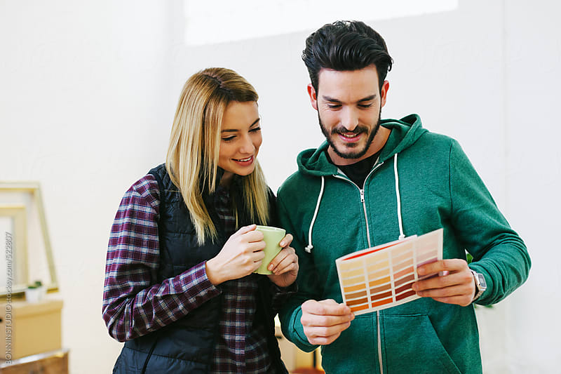 Young couple choosing swatch colours for the new home. by BONNINSTUDIO for Stocksy United