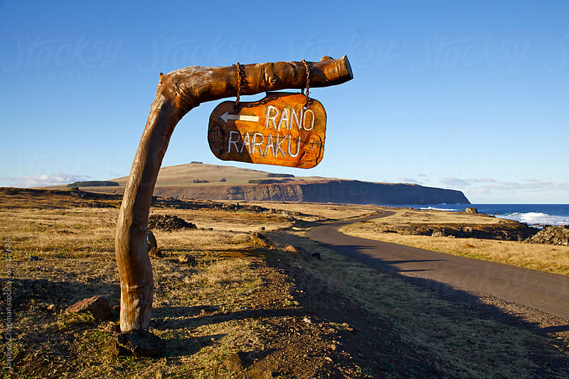 The Rano Raraka wooden sign post on the side of a road near the ocean, Easter Island by Jaydene Chapman for Stocksy United