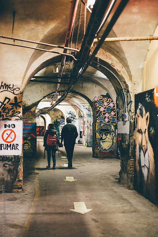Couple walking through a tunnel full of graffitis by María Barba for Stocksy United