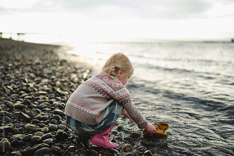 A Little Girl Crouches at the edge of the water with a crab shell by Amanda Voelker for Stocksy United