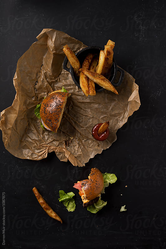 Burger and fries on brown paper on a dark background. by Darren Muir for Stocksy United