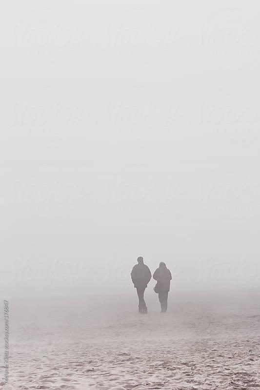 Couple walks on the beach on a foggy day by Melanie Kintz for Stocksy United