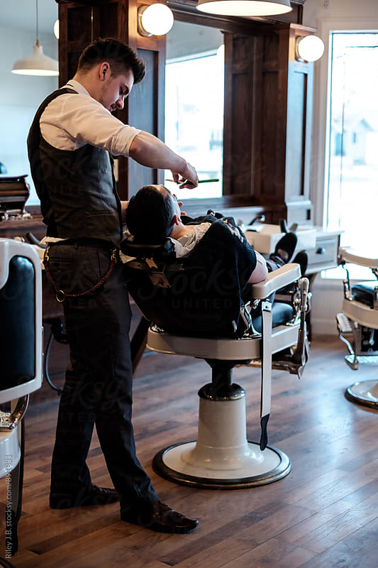 A gentleman barber shaving the face of a client that's reclined in a vintage barber chair. by Riley J.B. for Stocksy United