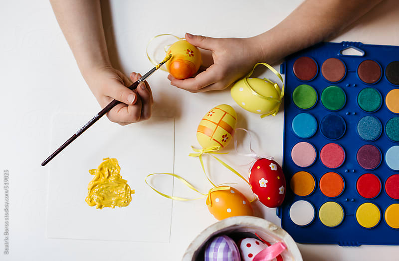 Hands painting yellow Easter eggs by Beatrix Boros for Stocksy United