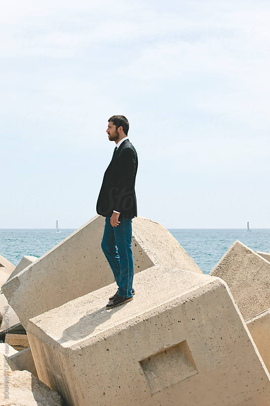 Businessman standing on breakwater. by BONNINSTUDIO for Stocksy United