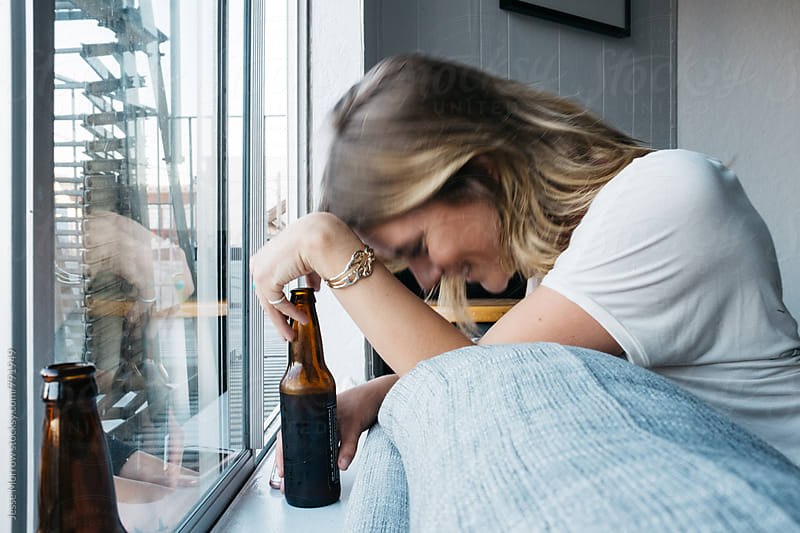 young blond drinking beer in apartment by Jesse Morrow for Stocksy United